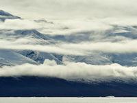 Verschillende lagen met nevel hangen boven het kustgebergte van Groenland. © Yves Adams