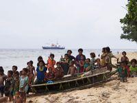 Het dorp Iwa met de lokale bevolking op enkele zelfgemaakte bootjes. De Spirit of Enderby op de achtergrond. © Heritage Expeditions