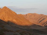 De zon gaat onder en hult de vallei in goudgeel licht. © Maarten Jacobs