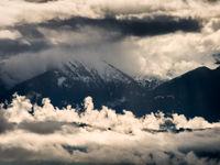 Een landschapsfoto vanuit de lucht, Parc naturel régional du massif des Bauges in de Savoie, in de Franse Alpen. De combinatie van wolkenformaties door slecht weer en warm zonlicht creëert een mysterieus effect. © Sebastian Vervenne