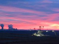 Een sfeerbeeld van de ondergaande zon met industrie op de achtergrond. © Stephan Kaasche