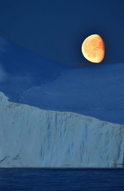 De maan geeft heel wat licht tijdens de noordelijke zomer en verlicht de ijsbergen. © Yves Adams