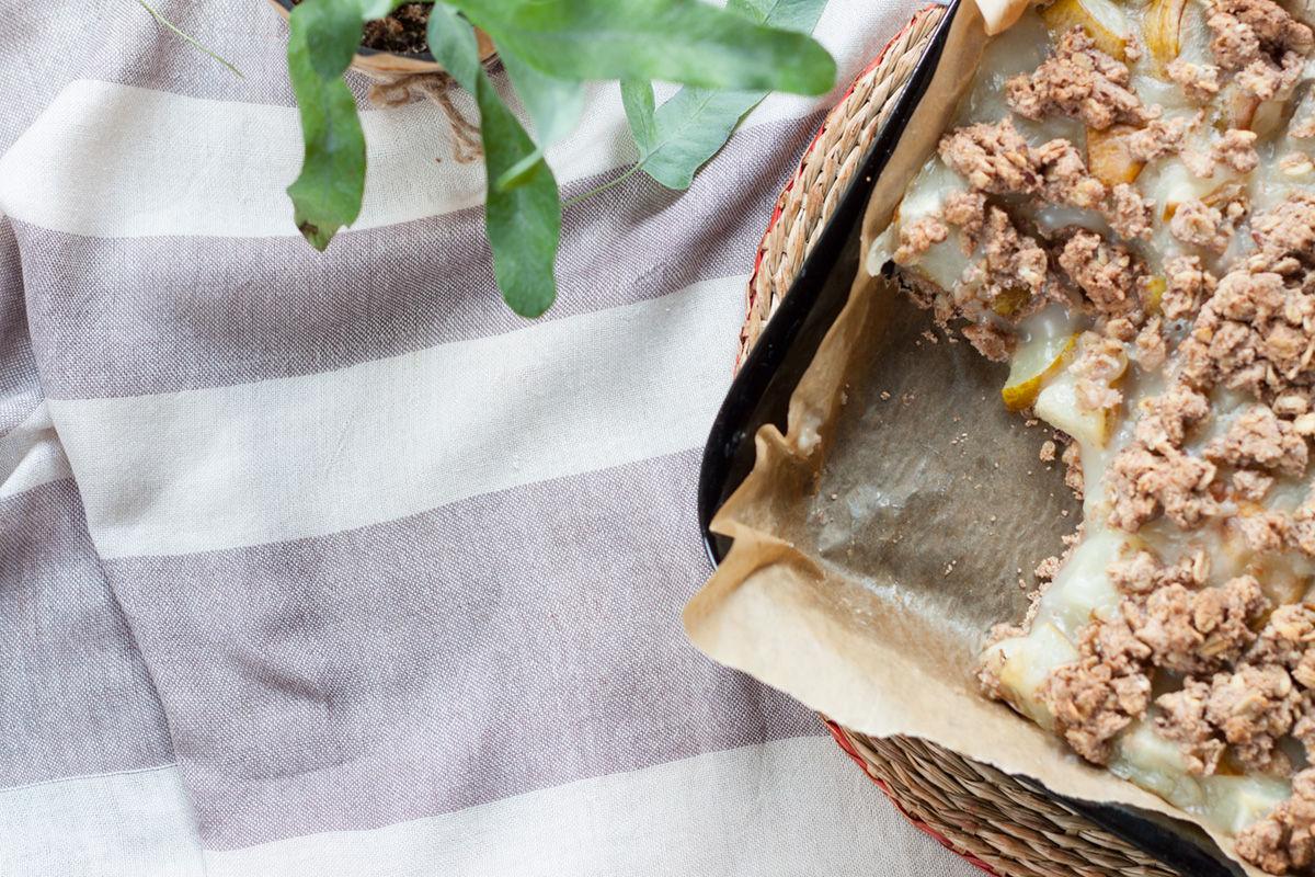 wegańskie gruszkowe ciasto bezglutenowe na wiklinowej podstawce i pasiastym materiale z paprotką