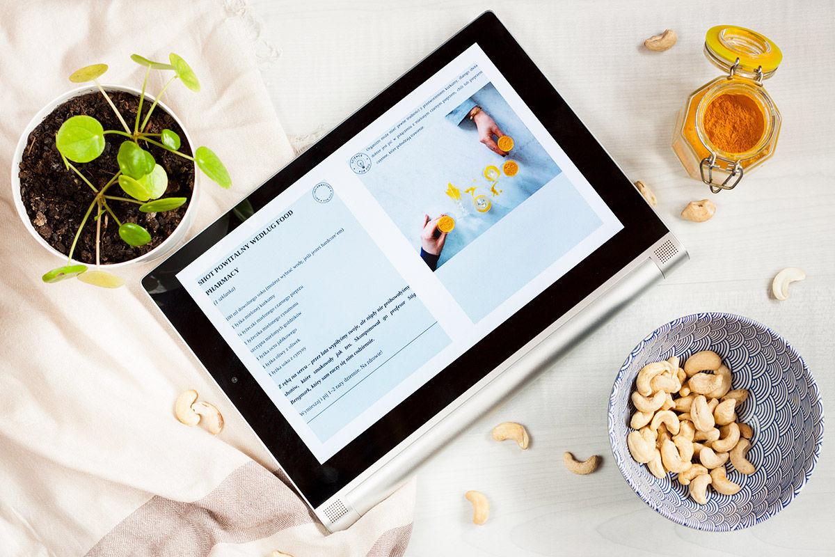 Tablet z fragmentem książki Food Pharmacy, kurkumą, orzechami nerkowca i rośliną