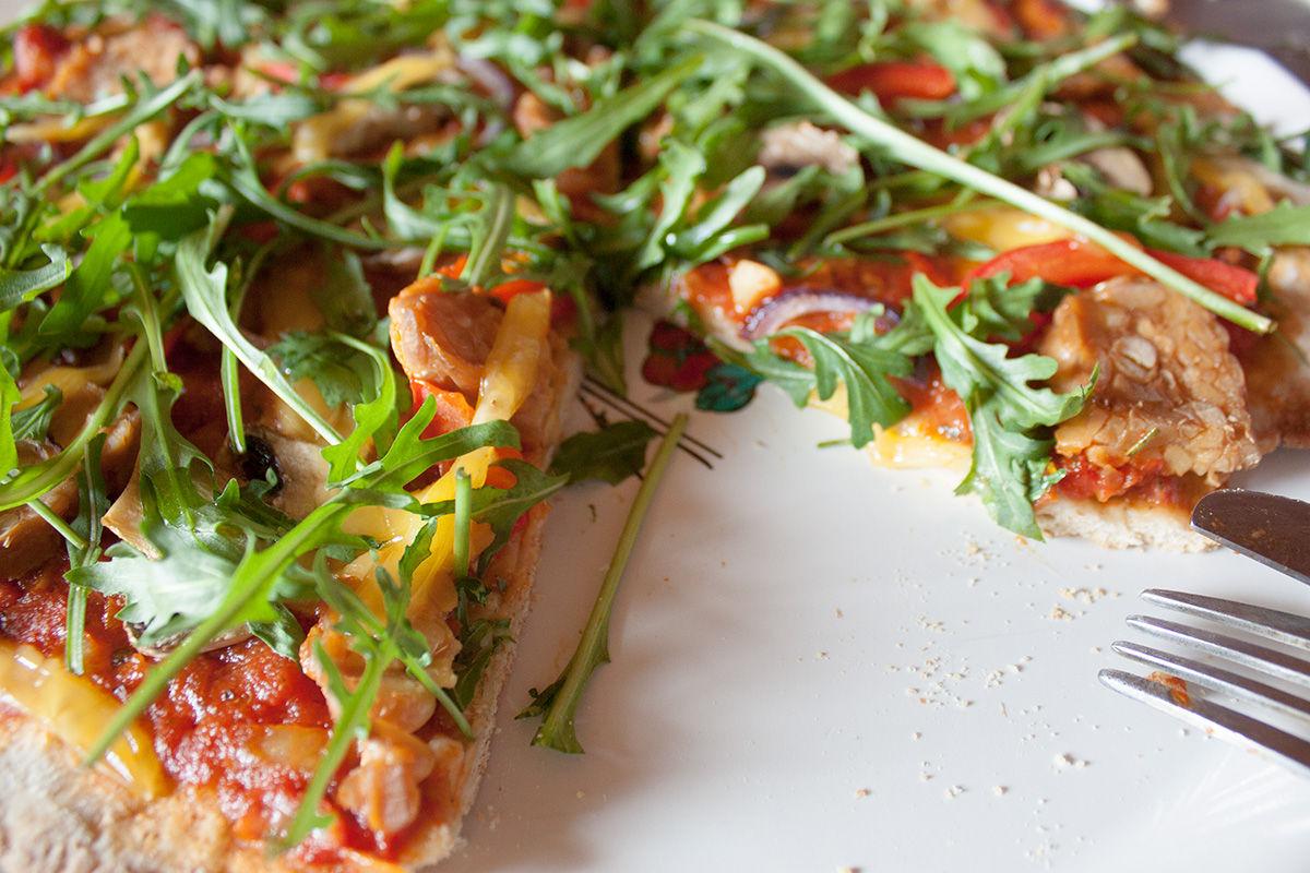 Wegańska pizza z rukolą, rośliną bogatą w chlorofil, food photography, zbliżenie na