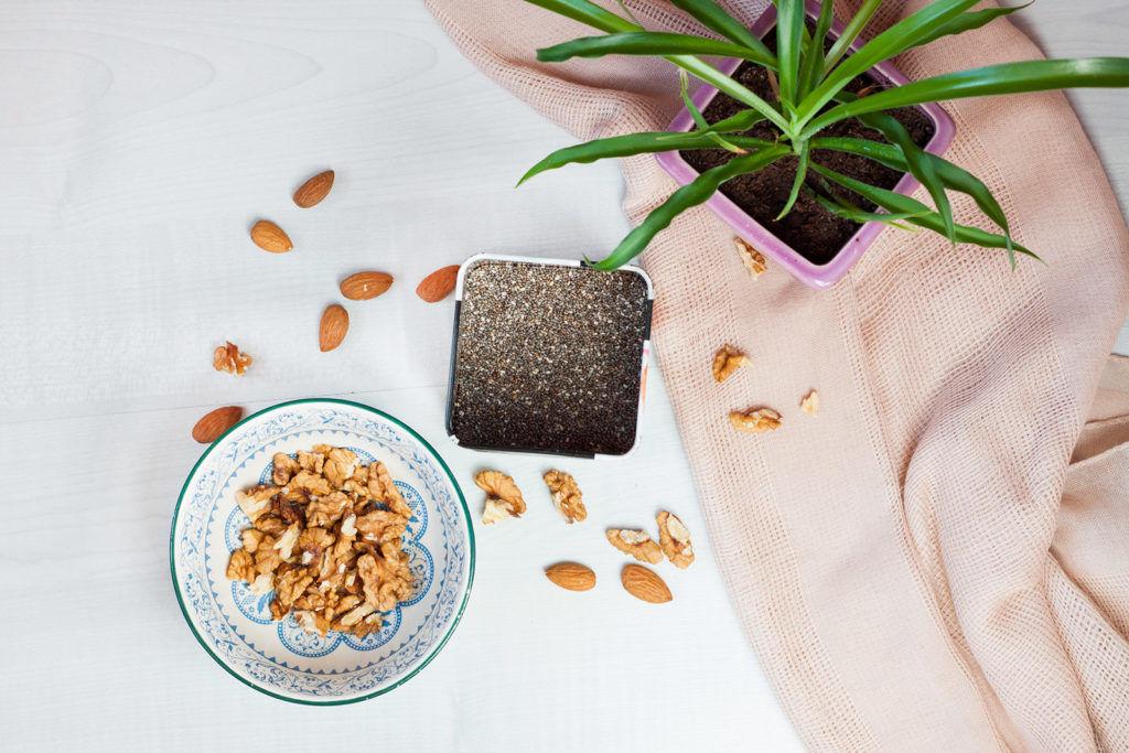 nasiona chia, orzechy włoskie, migdały na jasnym tle z roślinką
