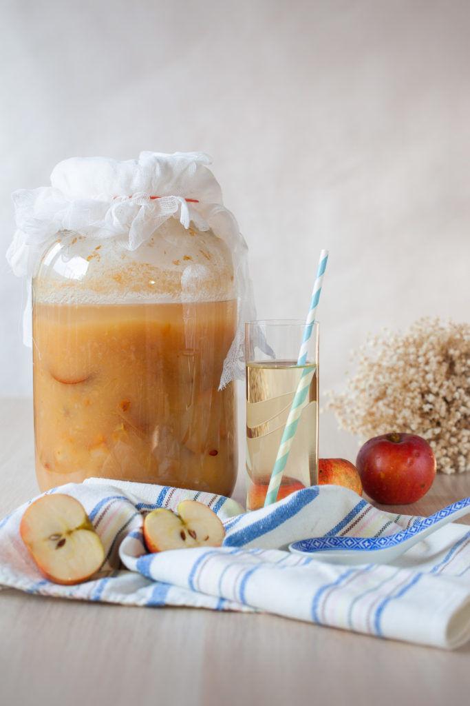 ocet jabłkowy w trakcie fermentacji w wielkim słoju, jabłka, ocet w szklance