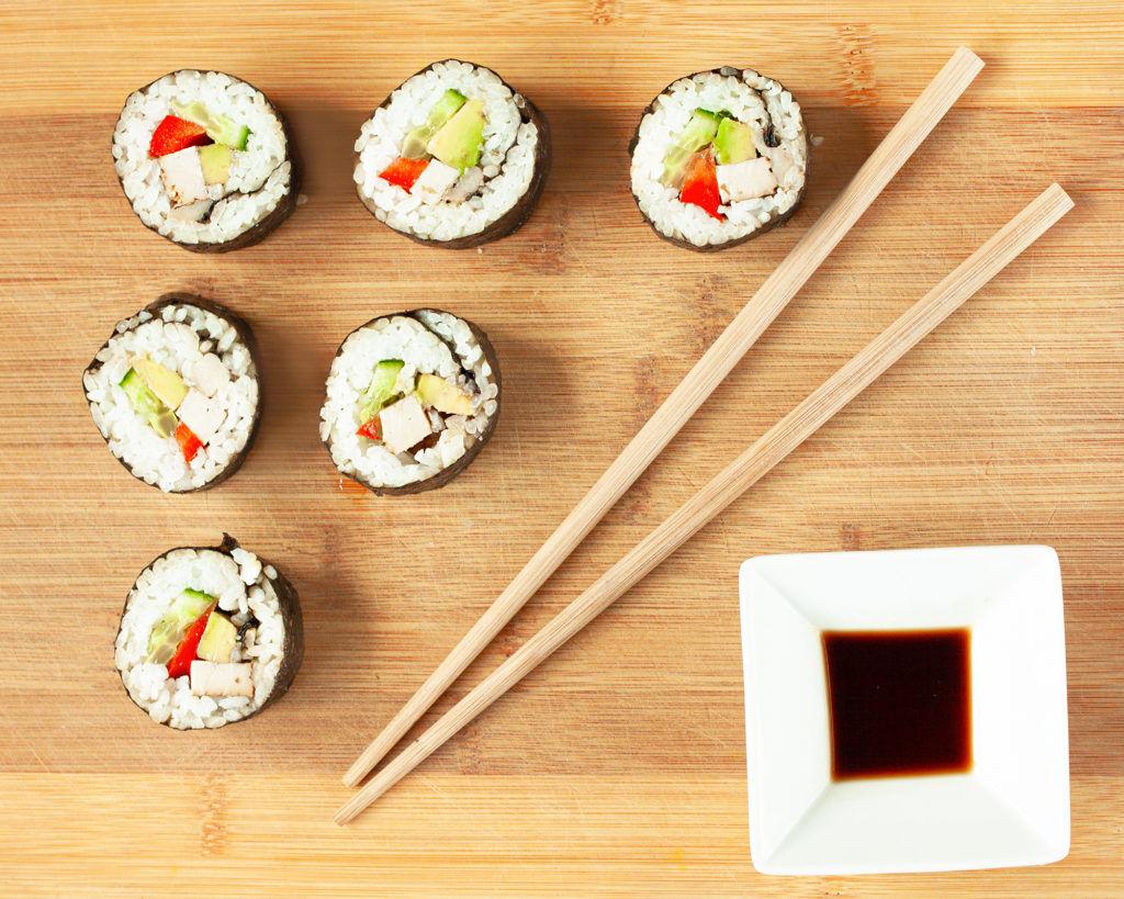 Wegańskie sushi z awokado i tofu pałeczki i sos sojowy na drewnianej desce
