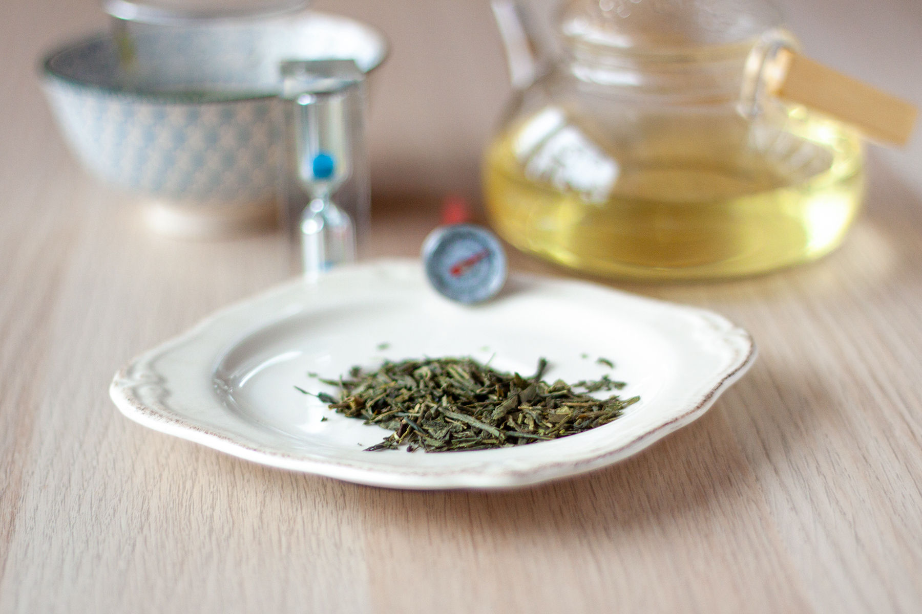 zielona herbata sencha, czajnik i termometr oraz klepsydra do mierzenia czasu parzenia
