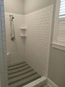 Ceramic tile shower walls with porcelain tile on floor
