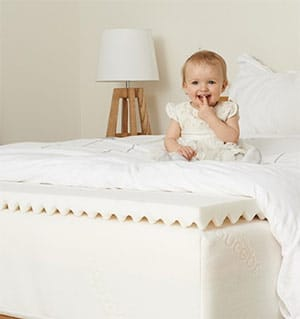cute baby on a mattress topper