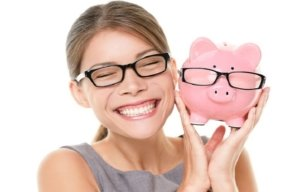 Image: smiling woman holds up her piggy bank
