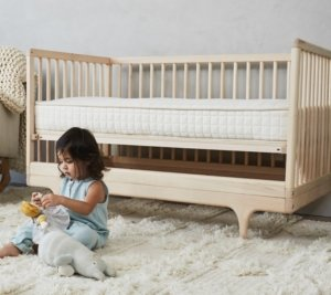 View of a toddler next to their Avocado Green Luxury Organic Crib Mattress