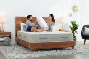 View of the Brentwood Cedar Mattress with a couple sitting on it.