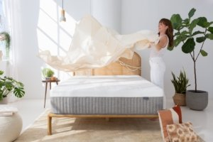 A lady setting sheets on the Cypress memory foam mattress