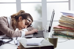 Burned out woman asleep at her desk, surrounded by unfinished work