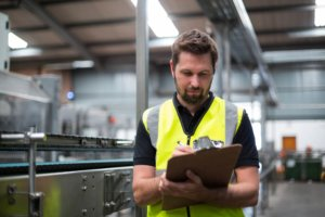 Factory worker consults clipboard
