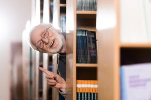 Image: Smiling librarian pokes his head out from behind a stack of books