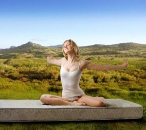 Woman stretches happily on a mattress in nature