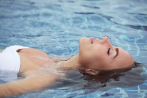Close up view of an attractive young woman floating in swimming pool