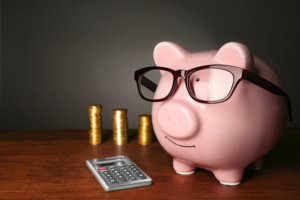 Image: piggy bank next to a calculator and three stacks of coins