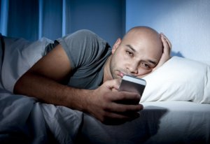 Image: Man in bed late at night, looking at his phone