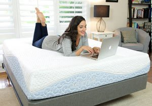 a girl working on her laptop lying on the Agility mattress