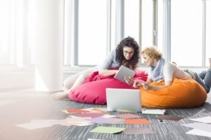 Image: two women on beanbag chairs doing work together