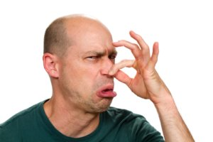 Man smells something stinky and pinches his nose to stop the bad odor.