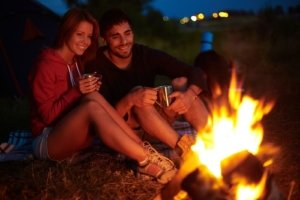 Image: happy couple sits beside a campfire