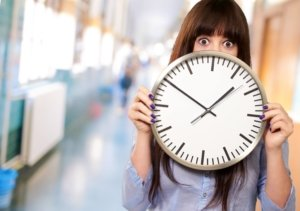 Image: surprised-looking woman holding clock