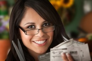 Image: Woman holds a pair of scissors and some coupons