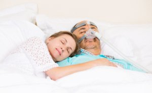 Image: man with CPAP machine sleeping with his wife