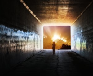 Image: A woman walks down a tunnel into a brilliant opening