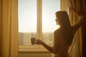 Image: Woman holding a cup of tea looks out through her windows at the early morning