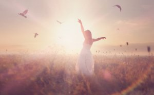 Image: A woman in a white dress stands in a field at sunset. She lifts up her hands to the sun and doves fly all around