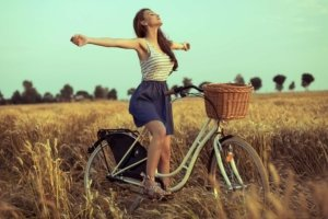 Image: woman on a bicycle stretches her arms out wide to the world, embracing the freedom of being alive