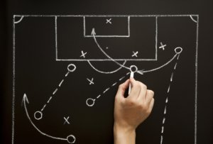 Image: hand on chalkboard drawing soccer game plan
