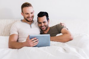 Image: happy gay couple in bed