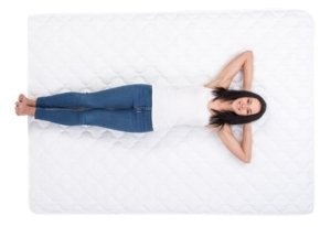 a girl lying on her back on a mattress