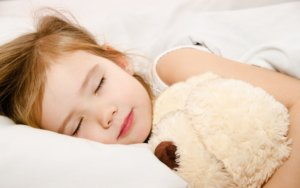 Image: little girl sleeps with a teddy bear