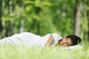 a young woman sleeping on grass