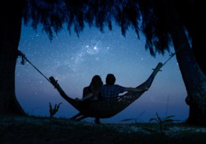 Image: A couple is sitting in a hammock, looking out at the Milky Way in all its majesty
