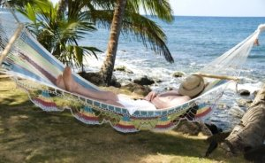 Image: a man is asleep in a hammock on the beach, hat tipped over his face