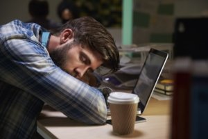 Office worker asleep at laptop
