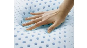 View of a hand pressing into the IDLE Sleep Pillow showing how soft it is
