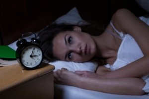 Image: woman with insomnia stares at the clock. It's the 3am. Why can't she sleep?