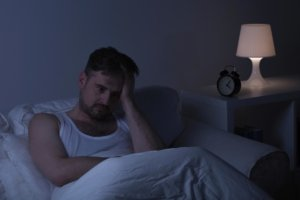 Image: man lies awake in bed, stressing about how late it is