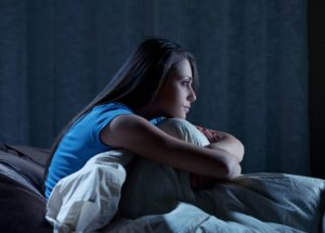 Image: insomniac woman sitting up in bed, knees tucked up to her chest