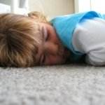 a kid sleeping on the carpet